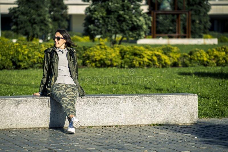 La muchacha joven y atractiva se está sentando en banco foto de archivo