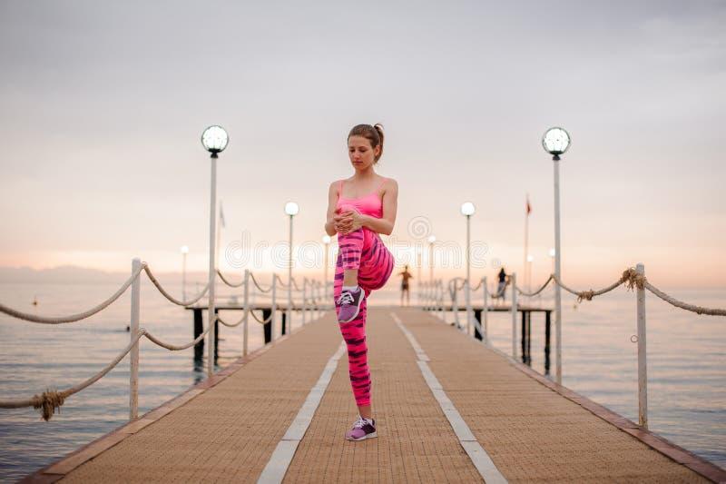 La muchacha joven y hermosa que hace mañana ejercita en el puente de madera imagenes de archivo