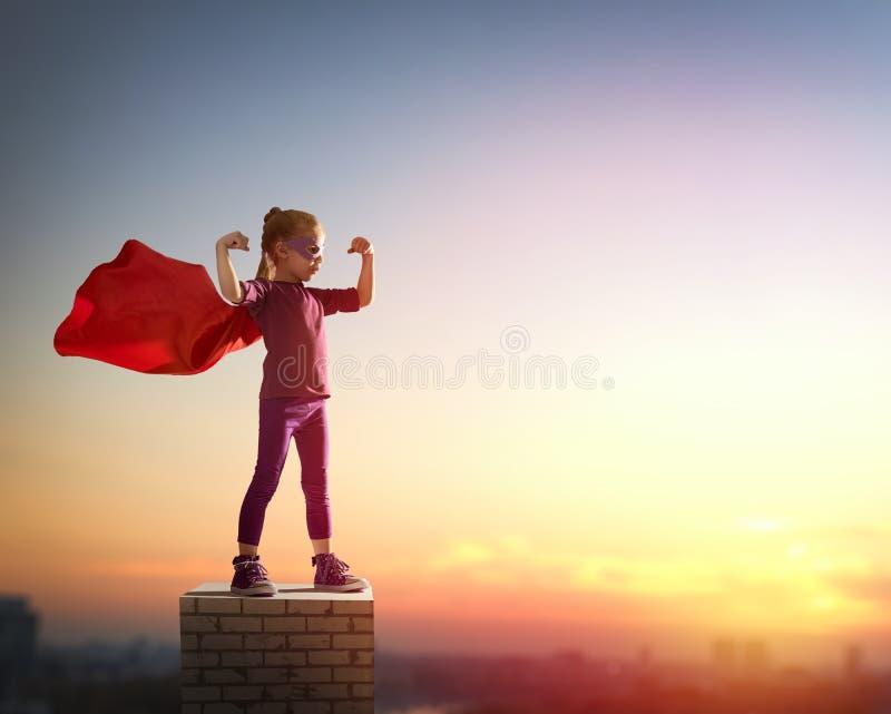 La muchacha juega al super héroe imagenes de archivo