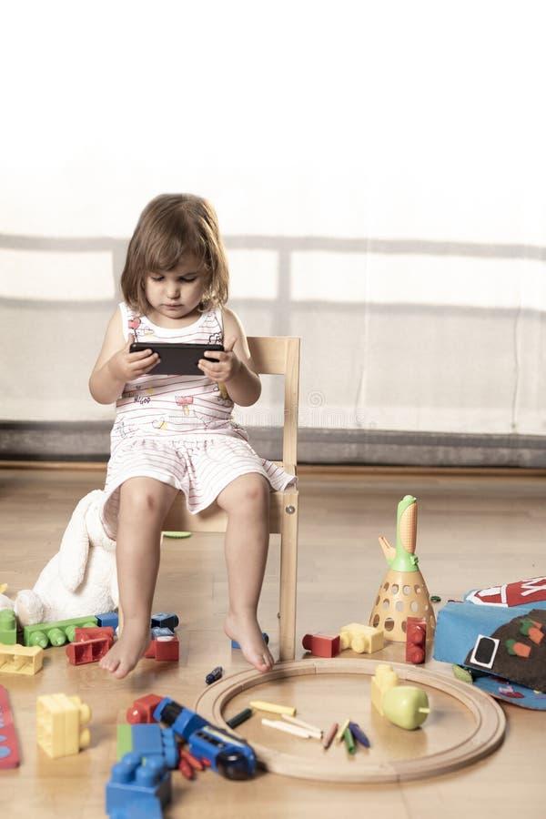 La muchacha juega el teléfono móvil Enganchan a la muchacha al teléfono móvil Él no juega con los juguetes El teléfono móvil es m imagen de archivo libre de regalías