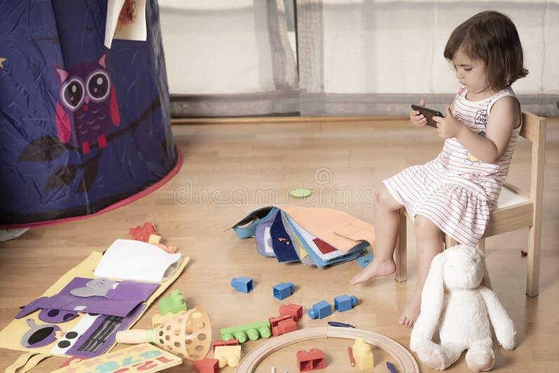 La muchacha juega el teléfono móvil Enganchan a la muchacha al teléfono móvil Él no juega con los juguetes El teléfono móvil es m fotos de archivo