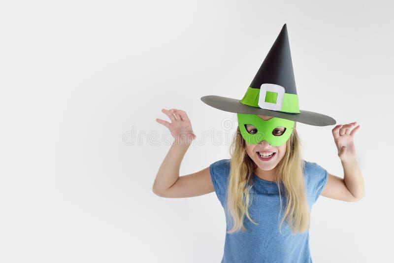 La muchacha juega en una máscara hecho a sí misma de la bruja para Halloween fotografía de archivo