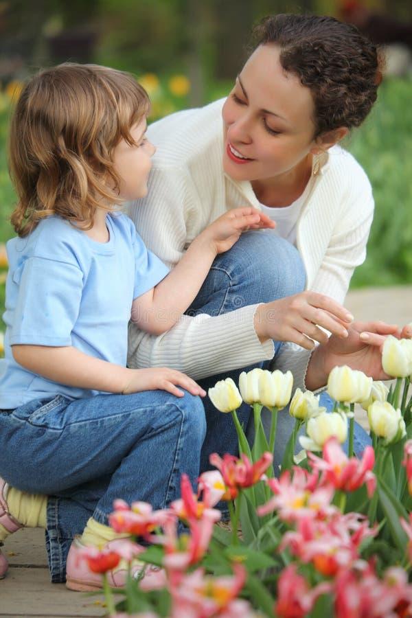La muchacha junto con madre se sienta en la cama con los tulipanes imágenes de archivo libres de regalías