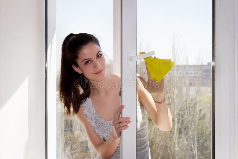 La muchacha lava una ventana fotos de archivo