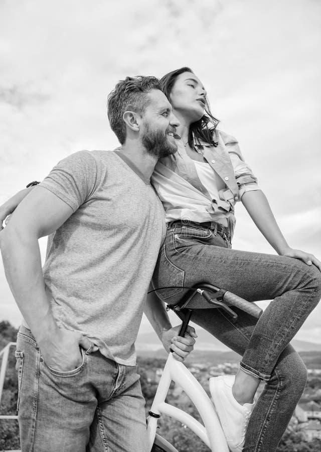 La muchacha le gusta él la monta en el manillar La muchacha se sienta en el manillar de su bici El machista barbudo del hombre mo imagenes de archivo