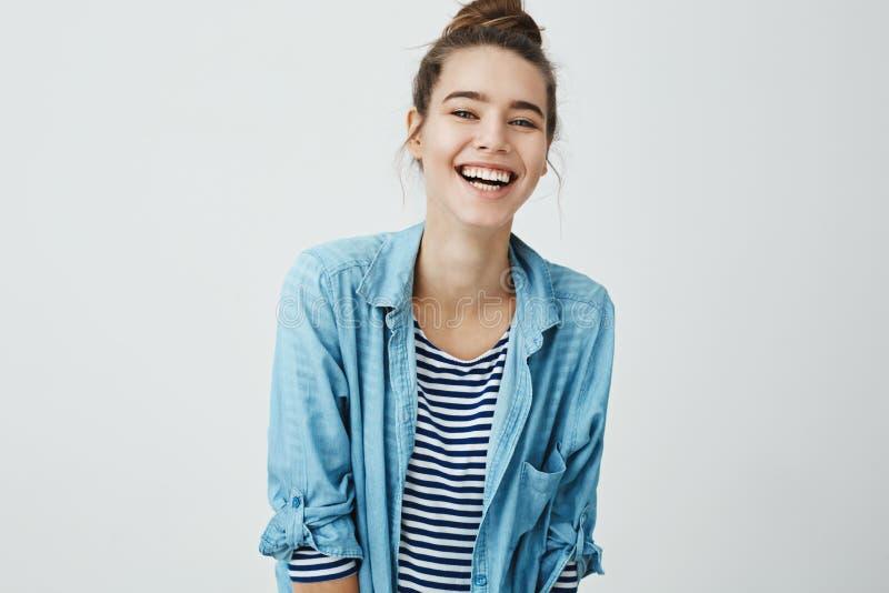La muchacha le gusta bromas divertidas Estudiante apuesto elegante con el peinado del bollo que tiembla de risa, sonriendo positi fotos de archivo