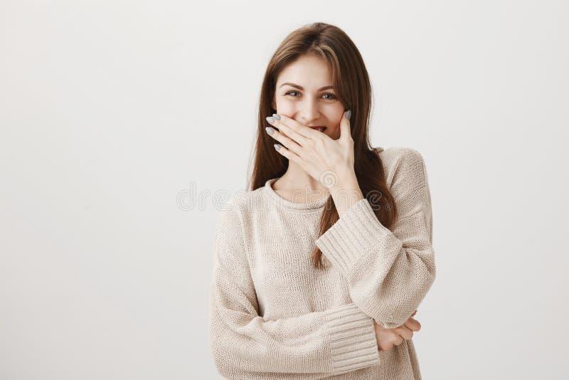 La muchacha le gusta bromas divertidas Hembra europea atractiva positiva que se ríe entre dientes y que cubre la boca con la palm fotografía de archivo