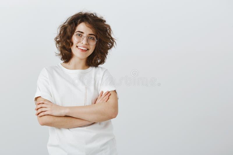 La muchacha le gusta trabajar en equipo Compañero de trabajo amistoso alegre en vidrios de moda con el pelo rizado corto, llevand imágenes de archivo libres de regalías