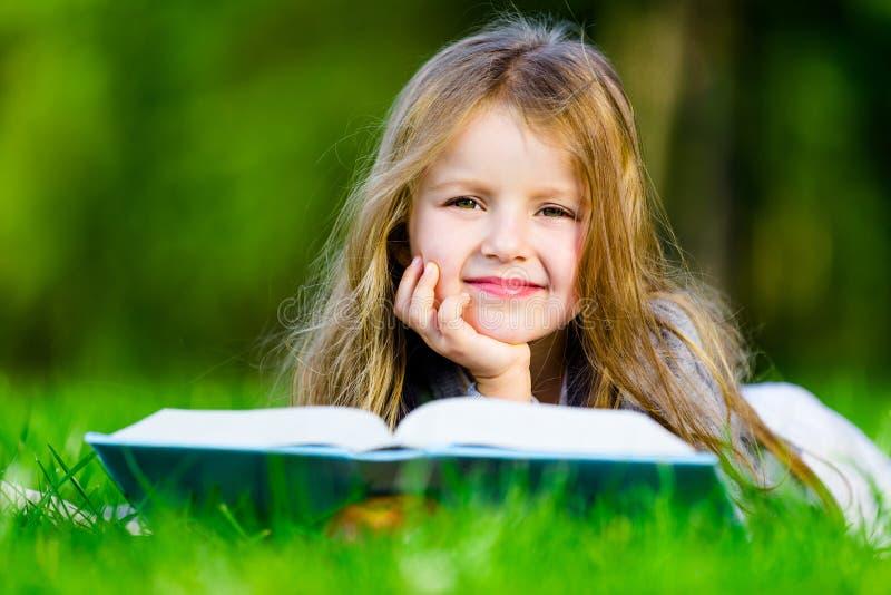 La muchacha lee el libro interesante en la hierba foto de archivo