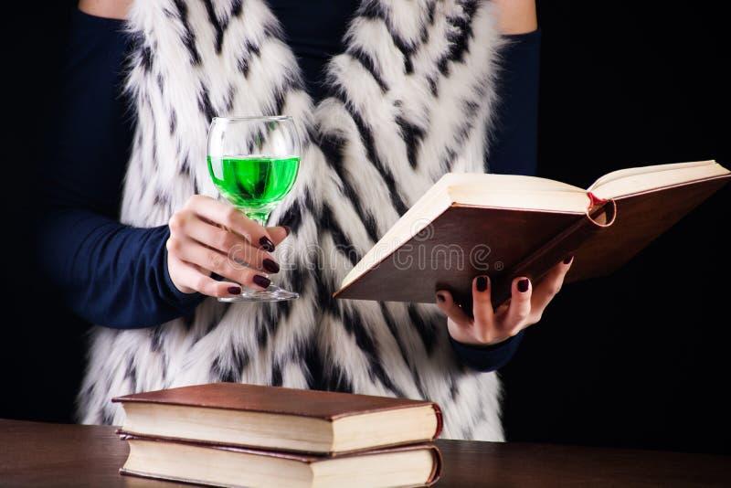 La muchacha lee el libro y bebe el ajenjo o la bebida de hadas verde foto de archivo