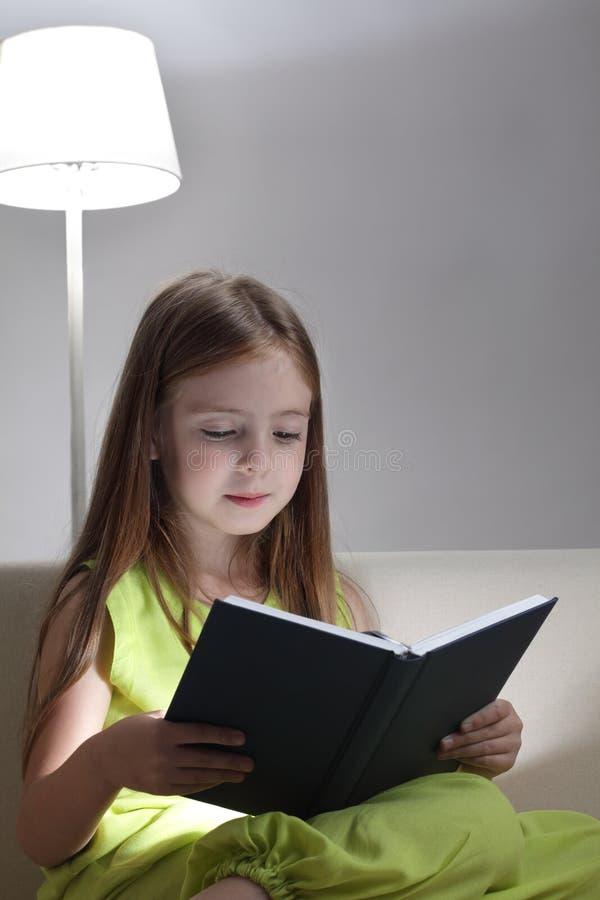 La muchacha leyó el libro en el sofá foto de archivo libre de regalías