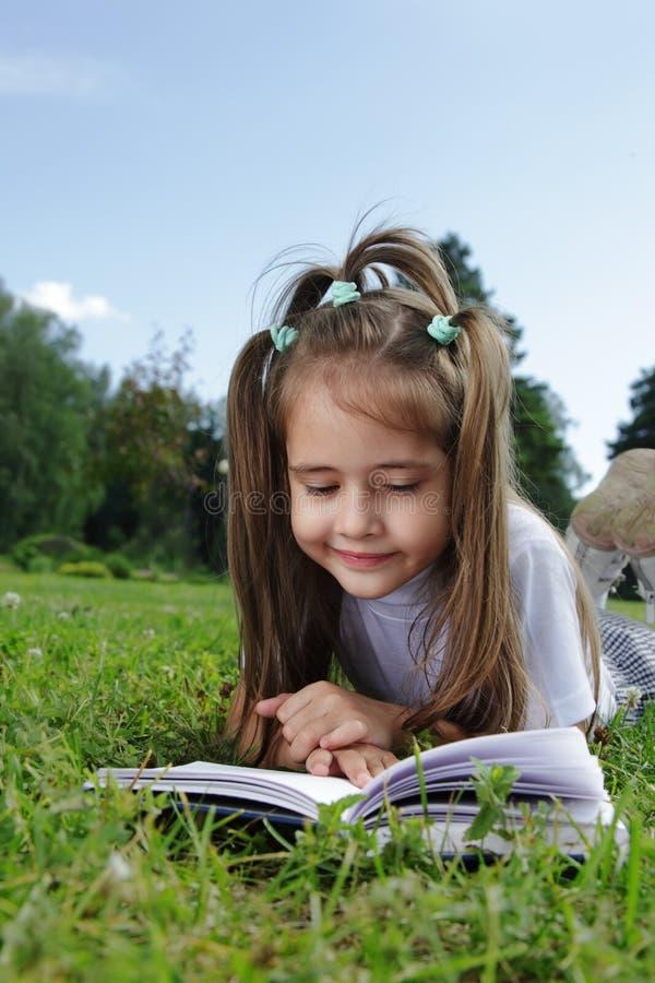 La muchacha leyó el libro en hierba fotos de archivo