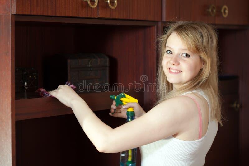 La muchacha limpia los muebles en el país foto de archivo