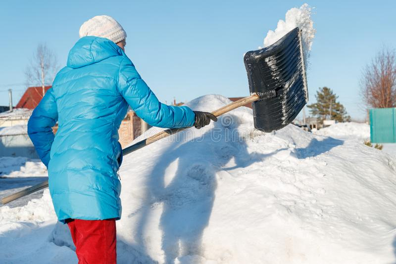 La muchacha limpia la pala de la nieve en el sitio cerca de su casa Luz del sol fotos de archivo libres de regalías