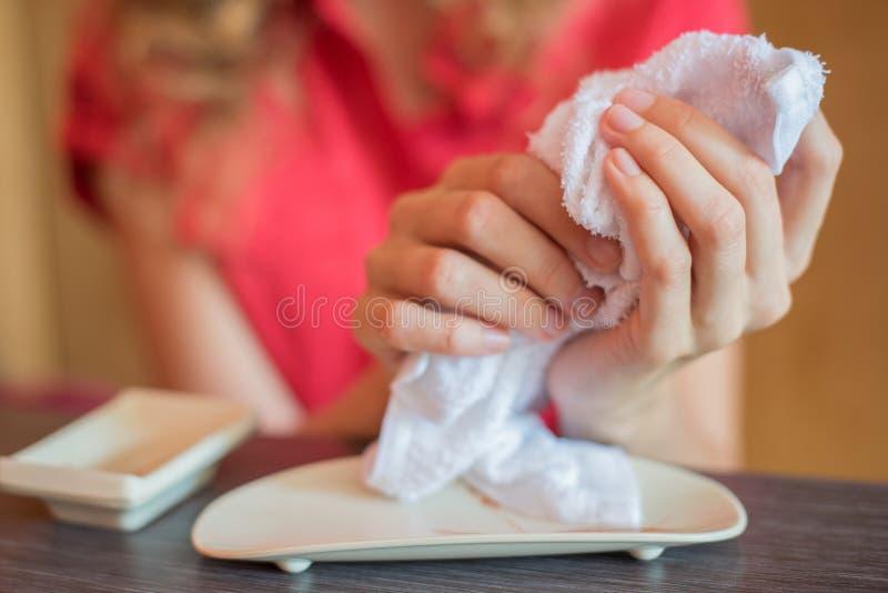 La muchacha limpia sus manos con una toalla caliente rodada en un rollo adentro imagen de archivo