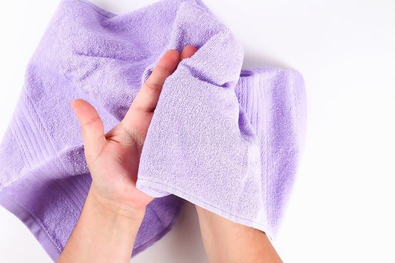La muchacha limpia sus manos con una toalla púrpura en el fondo blanco Visi?n superior imagen de archivo libre de regalías