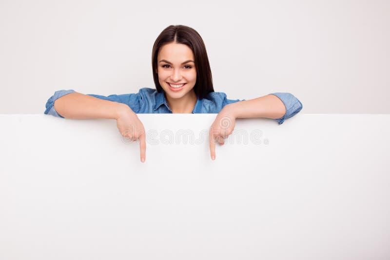 La muchacha linda alegre se está colocando detrás de la bandera en blanco blanca y foto de archivo libre de regalías
