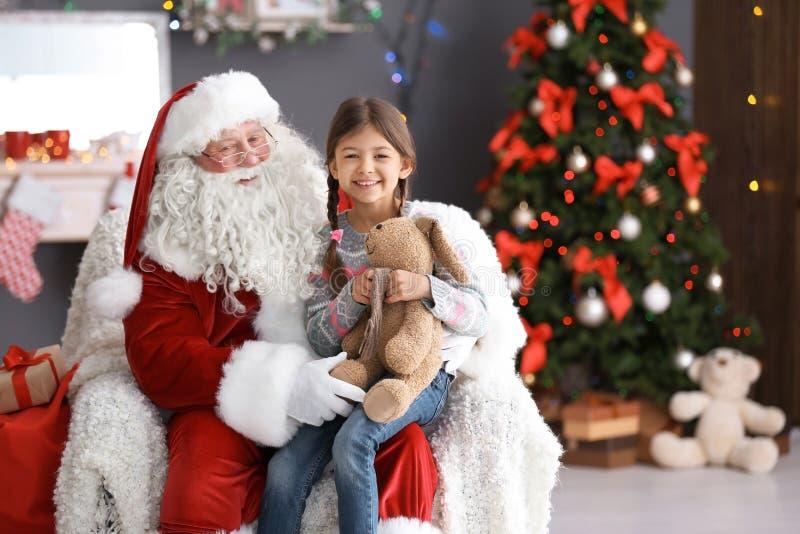La muchacha linda con el conejito del juguete que se sienta en el ` auténtico de Santa Claus traslapa dentro foto de archivo