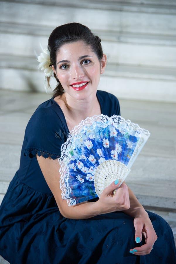La muchacha linda, con el vestido azul largo, con la fan, sentándose en fondo camina fotos de archivo libres de regalías