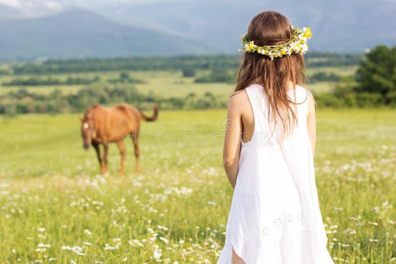 La muchacha linda del niño está mirando el caballo foto de archivo