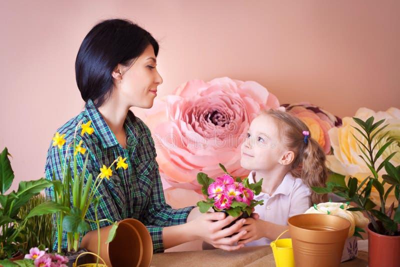 La muchacha linda del ni?o ayuda a su madre a cuidar para las plantas fotos de archivo
