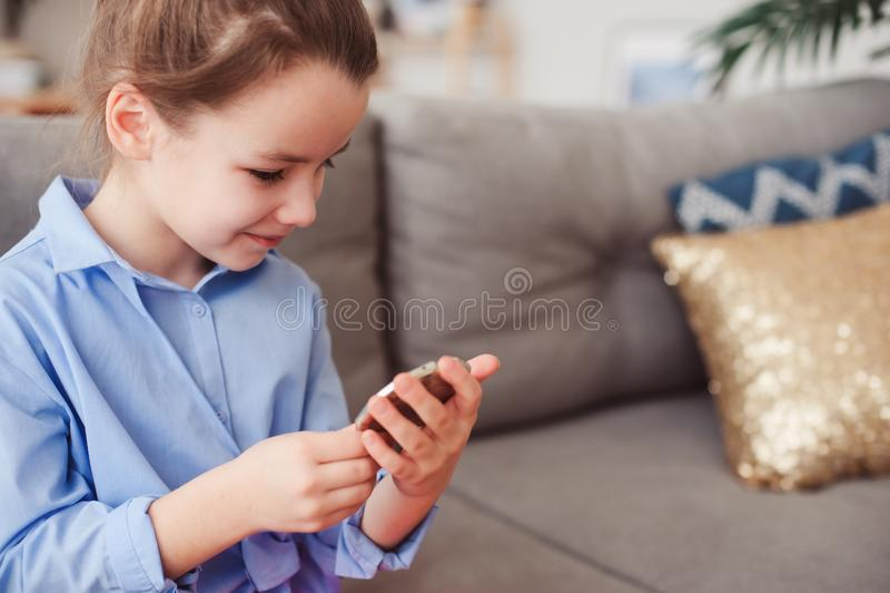 La muchacha linda del pequeño niño con el espejo y el cosmético empaquetan la comprobación del peinado en casa fotografía de archivo libre de regalías