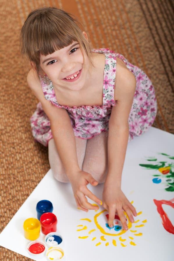 La muchacha drena las manos en el papel imagen de archivo libre de regalías