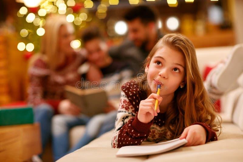 La muchacha linda escribe la letra a Santa Claus para la Navidad imagen de archivo