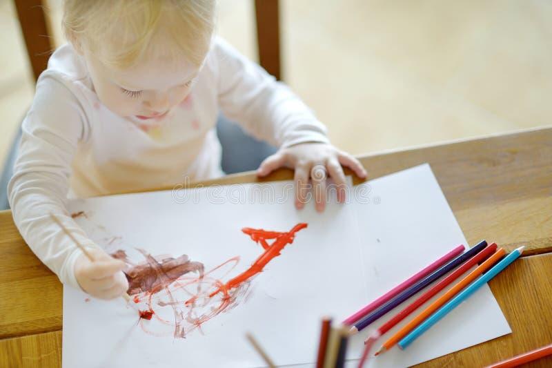 La muchacha linda está dibujando con las pinturas en preescolar imagen de archivo libre de regalías