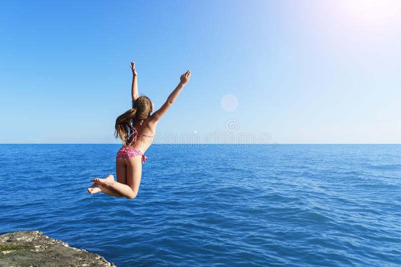 La muchacha linda europea joven es de salto y que vuela al mar azul tranquilo del rompeolas concreto hacia el sol suave del veran fotos de archivo libres de regalías