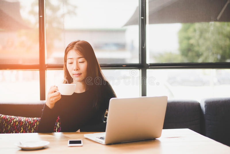 La muchacha linda hermosa de Asia en el café cerca de la ventana con la sonrisa y el espacio de trabajo del café, se relaja imagen de archivo libre de regalías