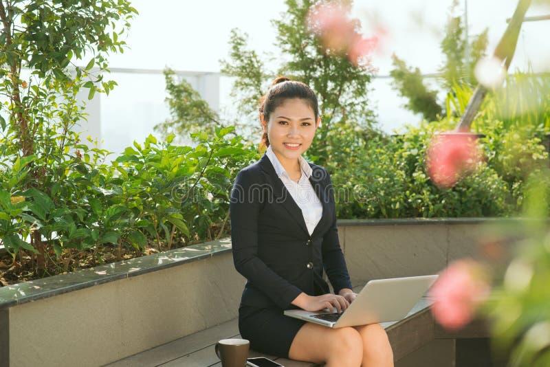 La muchacha linda hermosa que sonríe en mujer de negocios viste con el lapt imagenes de archivo