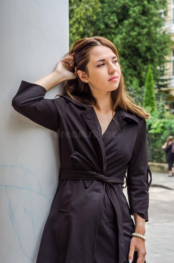 La muchacha linda joven con el pelo largo en una camisa y un dril de algodón pone en cortocircuito caminar en el parque en el día fotos de archivo