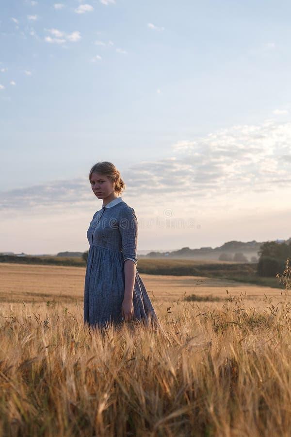 La muchacha linda joven en vestido azul con el pelo recogido mira la cámara en el campo de oídos la salida del sol Amanecer de ni imagen de archivo libre de regalías