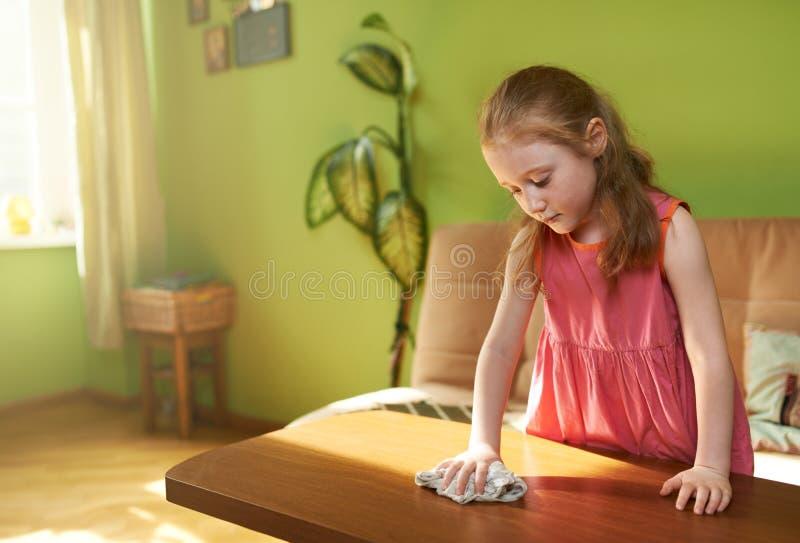 La muchacha linda limpia el polvo en la tabla foto de archivo