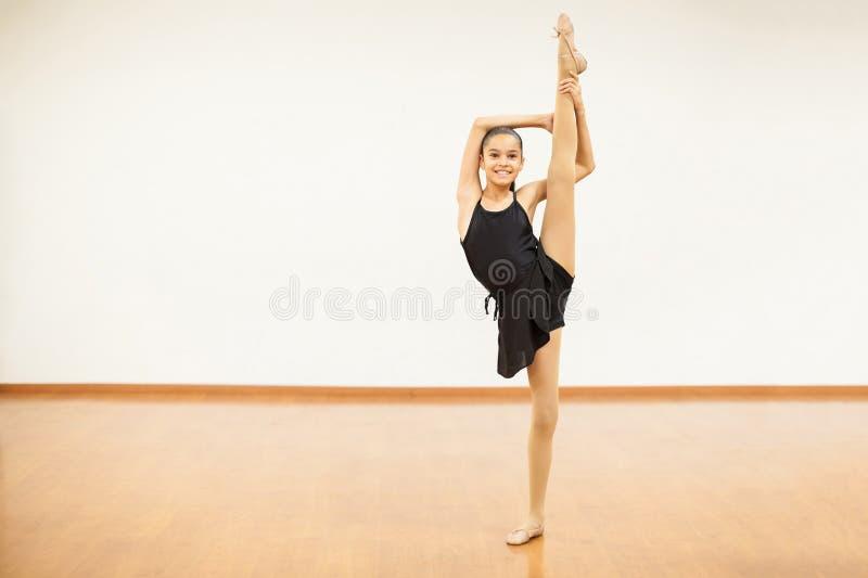 La muchacha linda que hacía una pierna partió en clase de danza fotografía de archivo