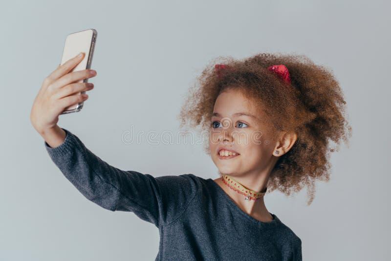 La muchacha linda sonriente con el pelo rizado hace el selfie con un teléfono en sus manos en un fondo gris imagenes de archivo