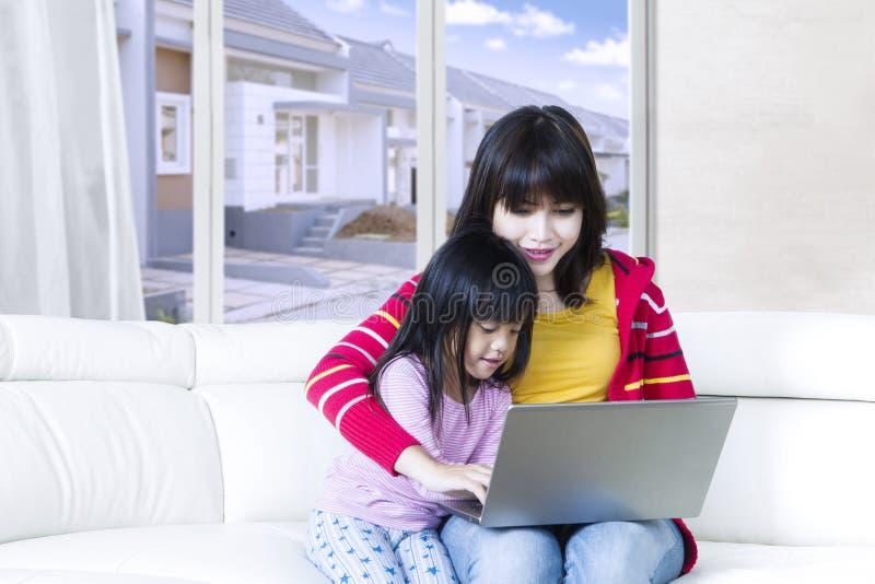 La muchacha linda utiliza el ordenador portátil con la madre imágenes de archivo libres de regalías