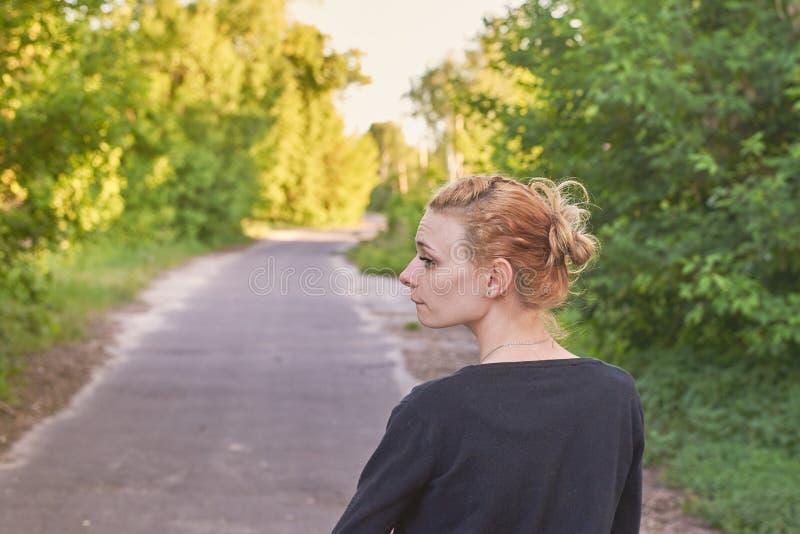 La muchacha linda va en una carretera de asfalto en naturaleza Visi?n trasera fotografía de archivo libre de regalías