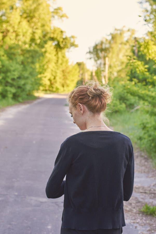 La muchacha linda va en una carretera de asfalto en naturaleza Visi?n trasera imagen de archivo