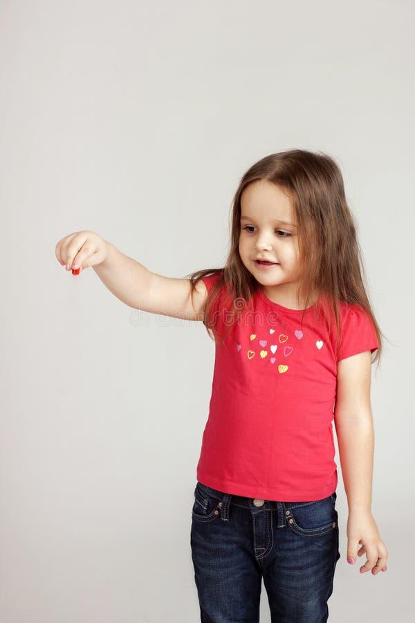 La muchacha lleva a cabo algo de su mano imagenes de archivo