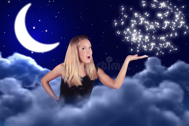 La muchacha lleva a cabo algo en la mano en cielo con la luna imagenes de archivo