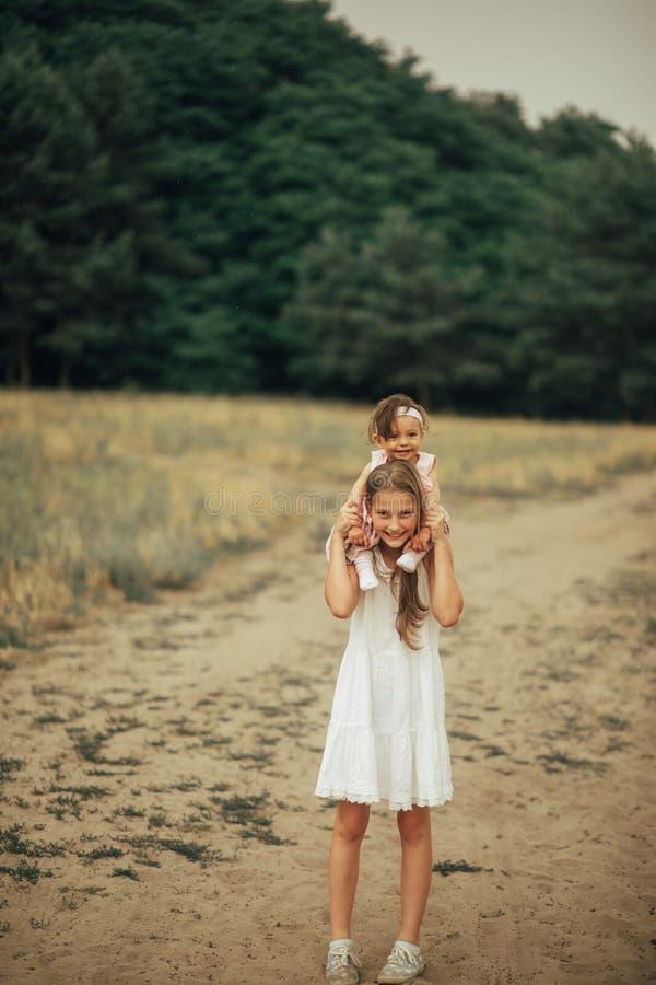 La muchacha lleva a su poca hermana en los hombros fotos de archivo libres de regalías