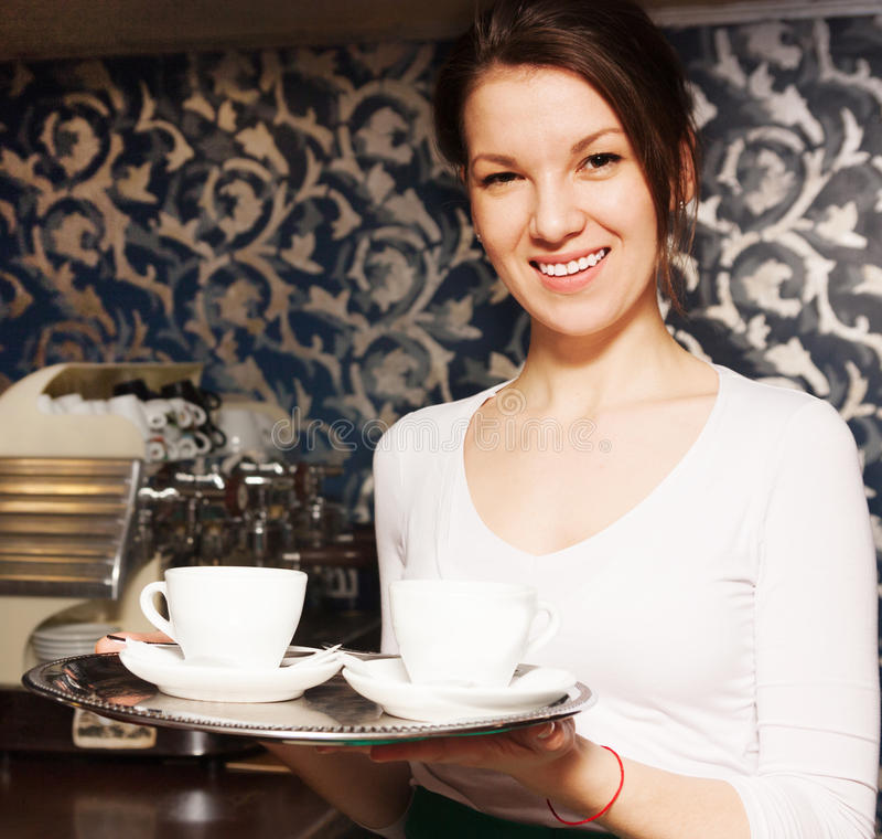 La muchacha lleva una bandeja de café imagen de archivo libre de regalías