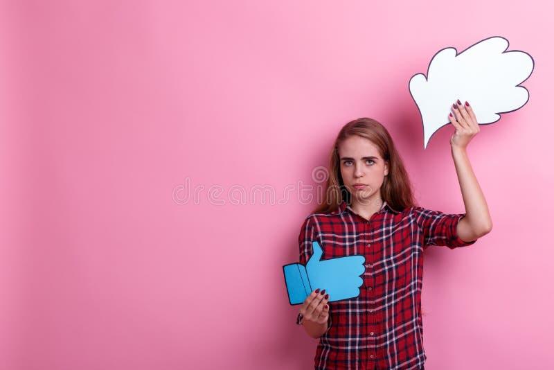 La muchacha, los controles una imagen del pensamiento o la idea tristes y los pulgares suben la muestra En un fondo rosado foto de archivo libre de regalías