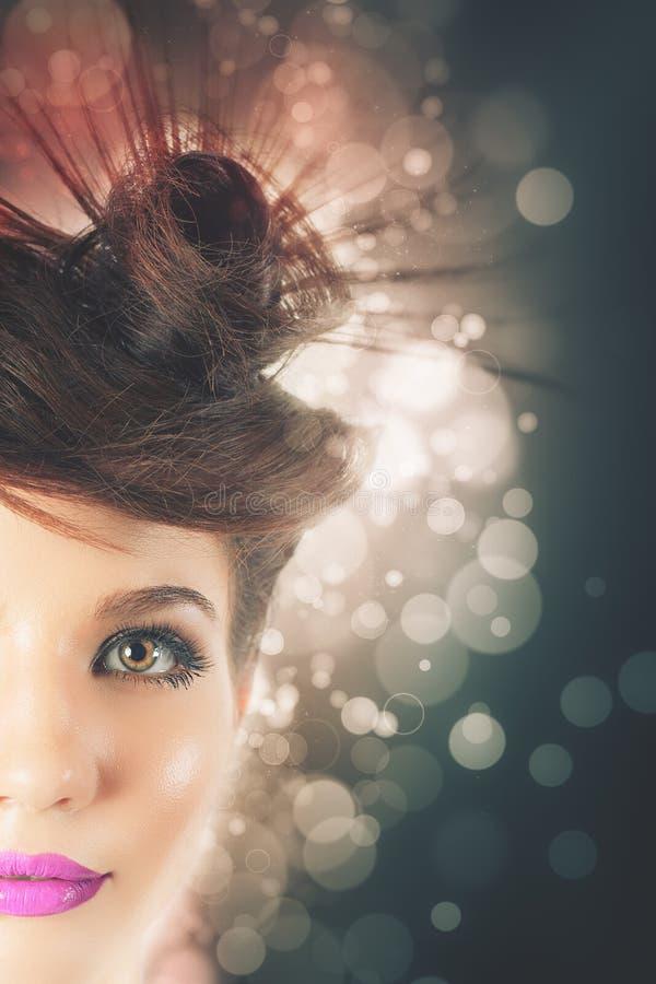 La muchacha magnífica con el peinado de lujo en el blanco empañó el fondo imagen de archivo libre de regalías