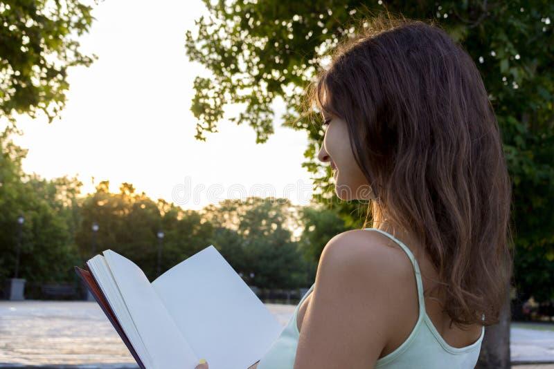 La muchacha magnífica goza el leer de un libro y de la puesta del sol El estudiante se está preparando para el examen o la prueba imagen de archivo
