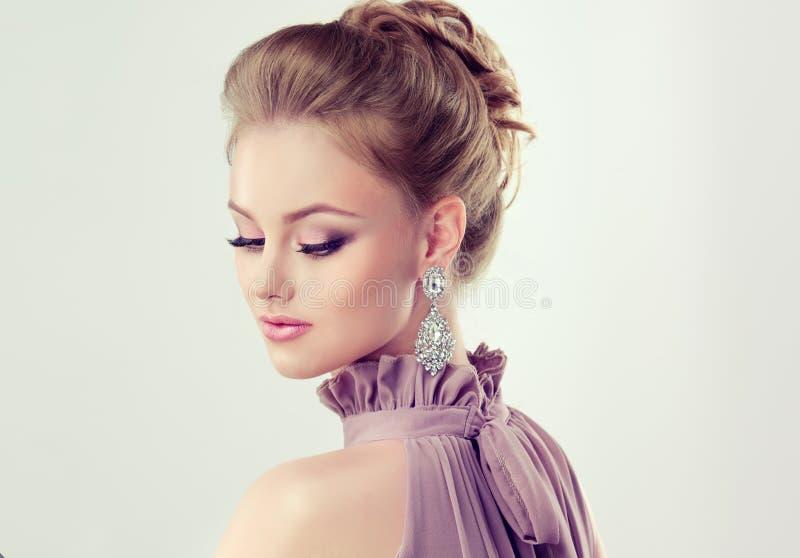 La muchacha magnífica joven se vistió en vestido de noche y maquillaje delicado encendido foto de archivo