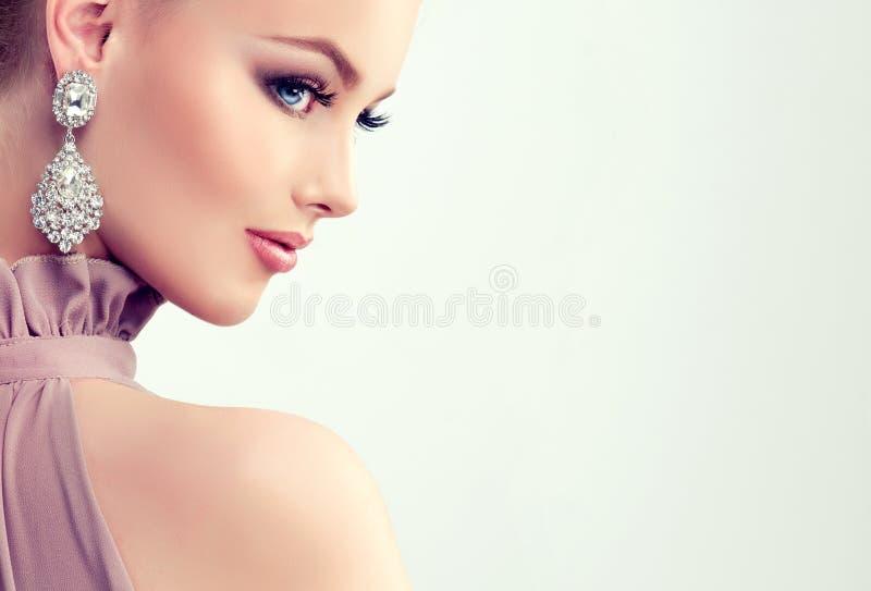 La muchacha magnífica joven se vistió en vestido de noche y maquillaje delicado encendido foto de archivo libre de regalías
