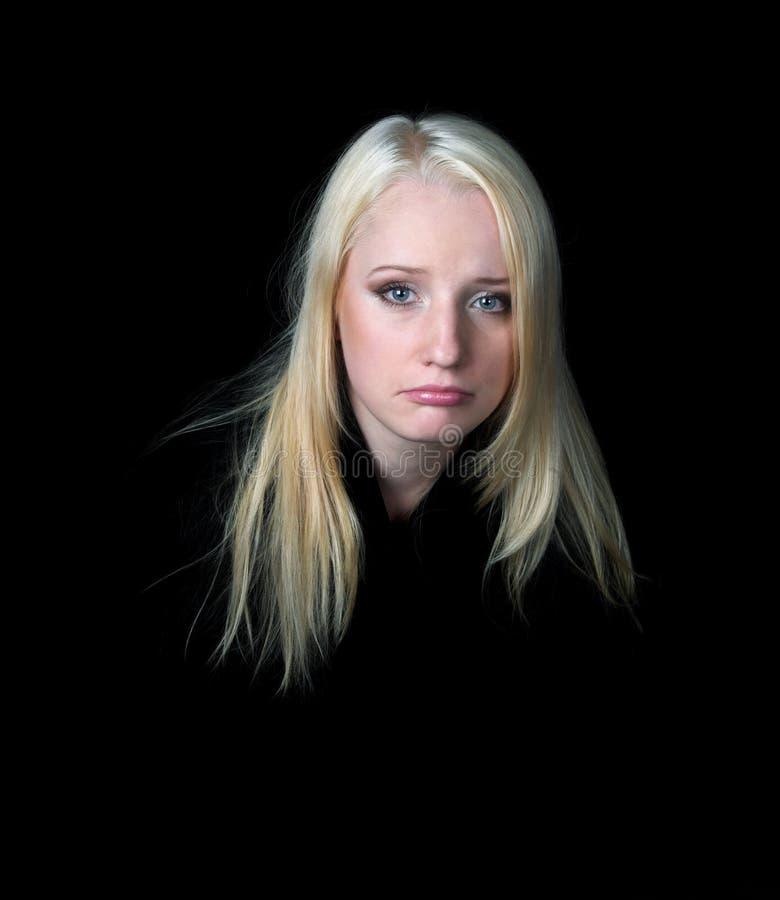 La muchacha melancólica en un fondo negro.